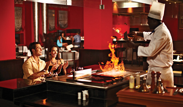 Un couple admirant un chef grillant des aliments au style teppanyaki