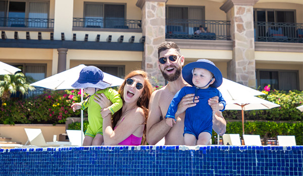 Mom and dad in the pool holding up two babies wearing sun hats