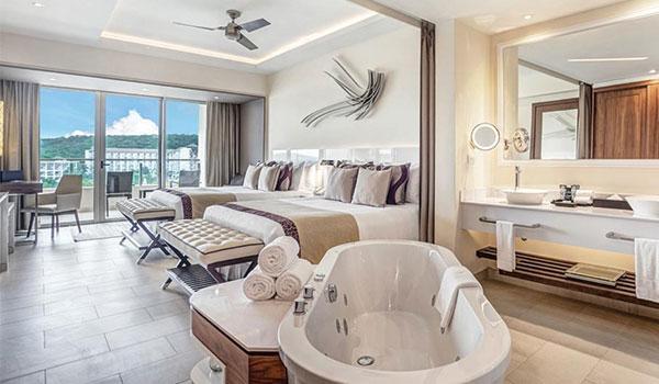 Chambre spacieuse avec deux lits et un jacuzzi donnant sur la mer