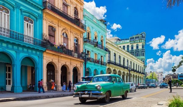 Classic American car driving past colonial buildings in Havana
