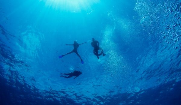 Three people scuba diving in the blue waters of Cancun