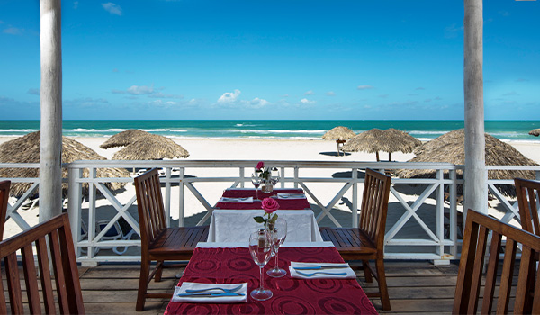 Romantic dinner table on a patio by the beach