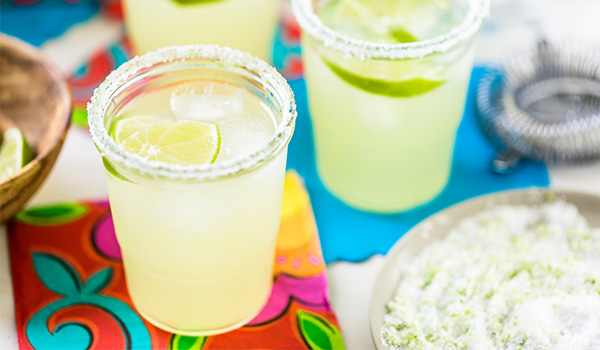 Two margaritas with salty rims sitting on a colourful table cloth