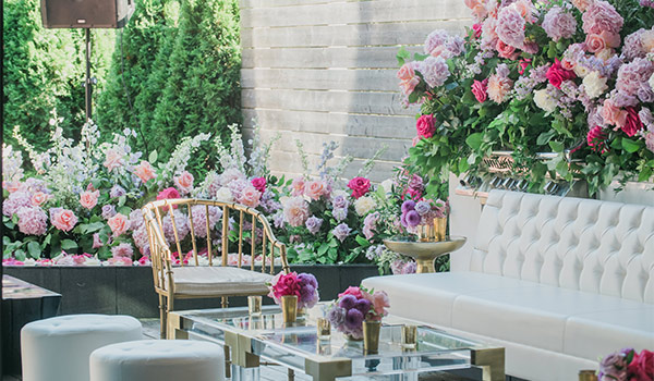 Lounge area surrounded by lush foliage and pastel flowers