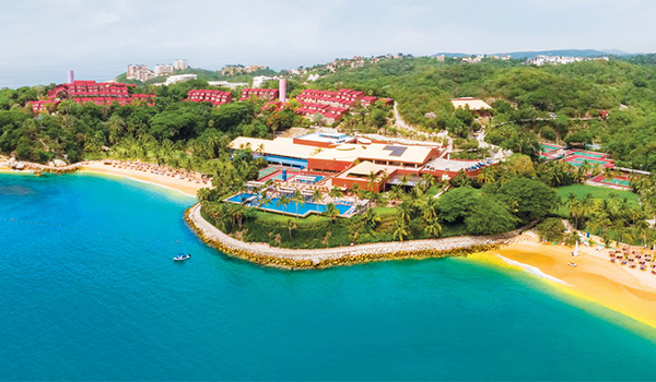 Aerial shot of resort overlooking the ocean with two golden-sand beaches
