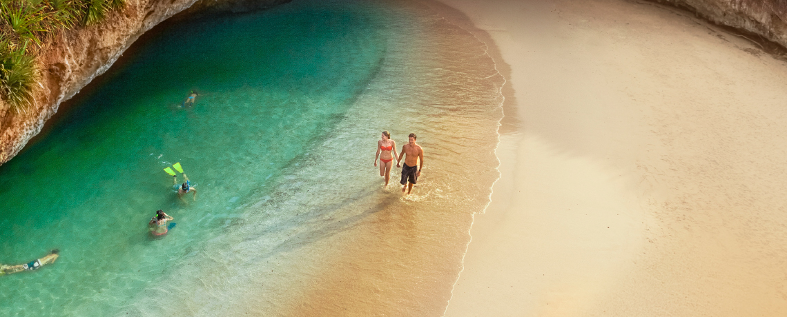 Couple walking along a beach side cenote