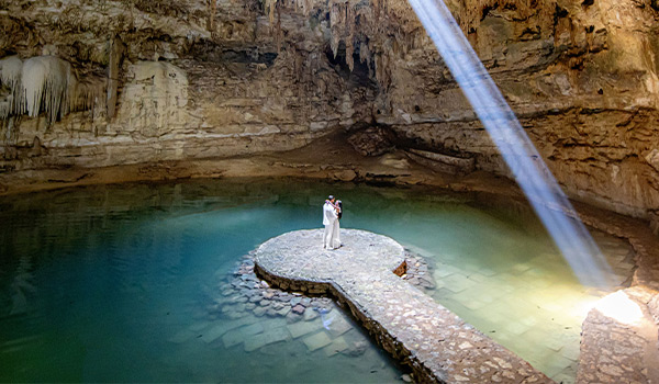 Bride and groom standing in a cenote