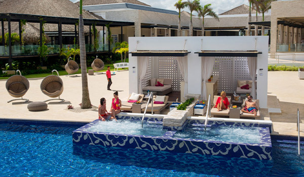 Vacationers lounging in a private luxury cabana with Jacuzzi