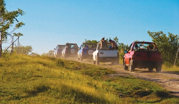 Convoy of open-air Jeeps driving down a trail in the Cuban countryside