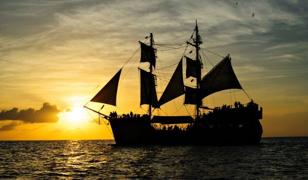 Silhouette of a pirate ship sailing through the sea at sunset