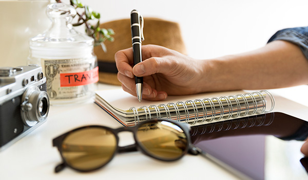 "Person writing in a notebook with a tablet, sunglasses and jar with ""travel fund"" written on it"