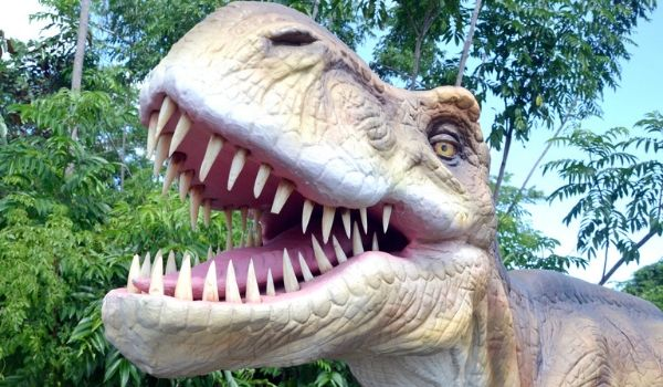Animatronic dinosaur with its mouth open in a forest