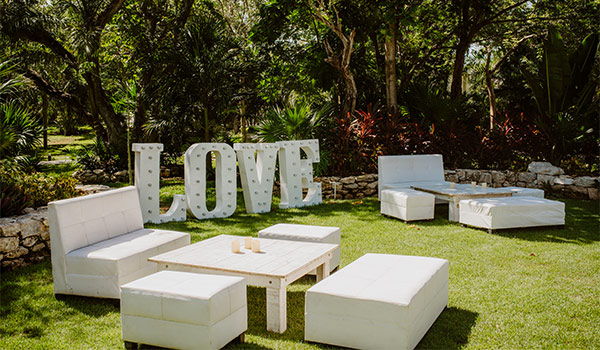 Couches in a garden with a marquee sign