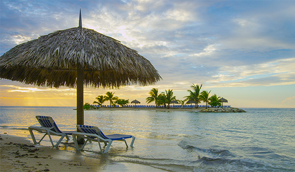 Sun loungers under palapa with private beach in the distance