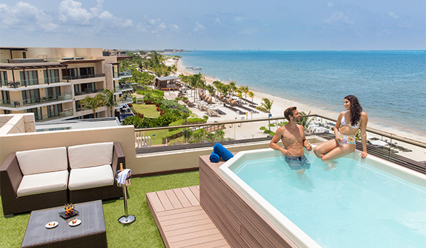 Couple sitting in a Jacuzzi on a rooftop overlooking the ocean