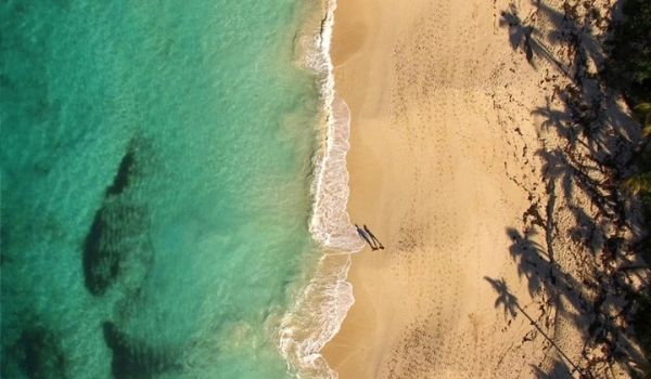 Aerial view of man and woman walking on Paradise Beach