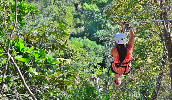 Woman zip lining through a verdant jungle in Costa Rica