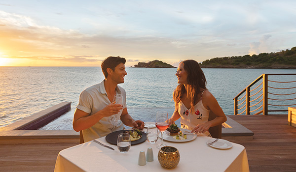 Couple eating dinner at a private table on a balcony overlooking the ocean at sunset