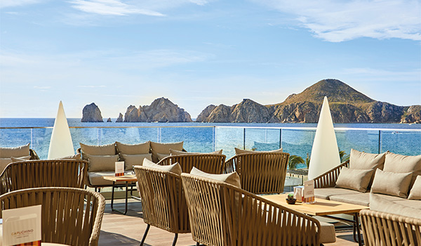 Outdoor coffee shop with comfortable chairs overlooking the rocky coast of Los Cabos
