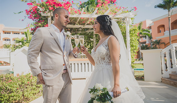 Bride and groom holding champagne glasses in a garden
