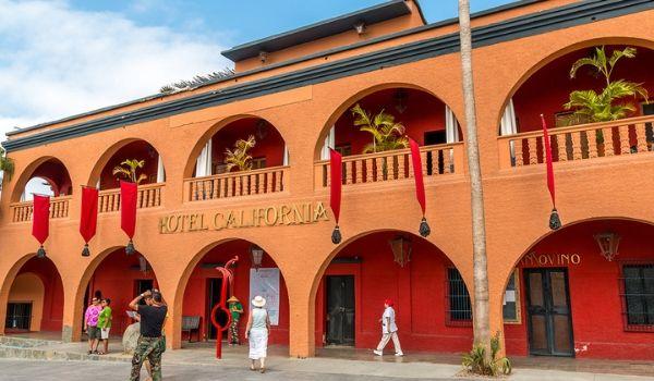 Personnes prenant des photos de l'extérieur de l'Hotel California et de son architecture ancestrale.