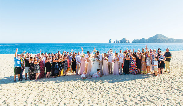 Groom and bride posing with all their guests on the beach