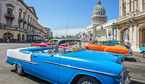 A bright blue classic car parked on a historic street in Havana