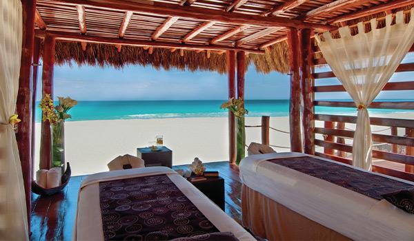 Deux tables de massage sous un palapa à la plage