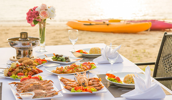 Table on a beach laden with food with kayaks in the background