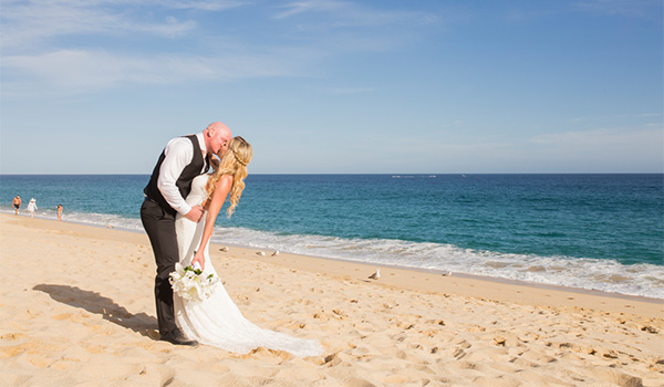 Groom and bride kissing on the beach