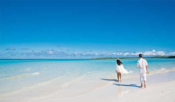 Man and woman walking on the pristine shores of Playa Paraiso