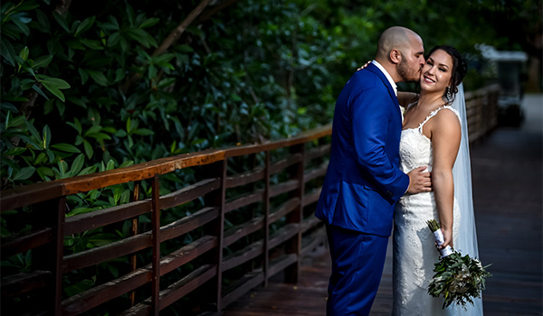 Bride and groom posing on a bridge in the forest