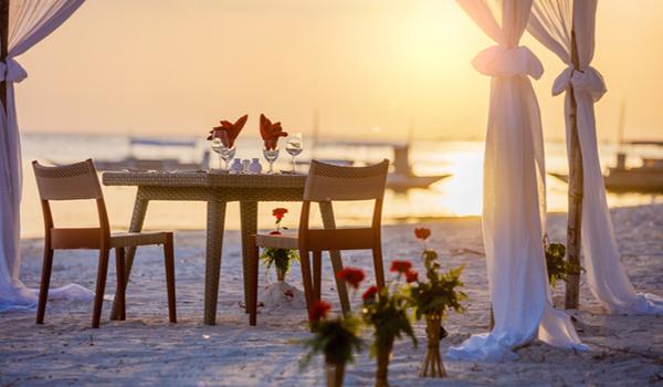Une table et deux chaises installées pour un souper romantique sur une belle plage