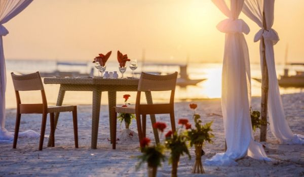 Table and two chairs set for a romantic dinner on beautiful beach