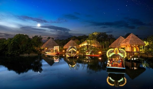 River boats cruising down a hut-lined waterway at night