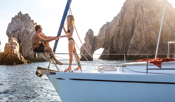 Couple standing on the deck of a catamaran cruising along the coast of Los Cabos