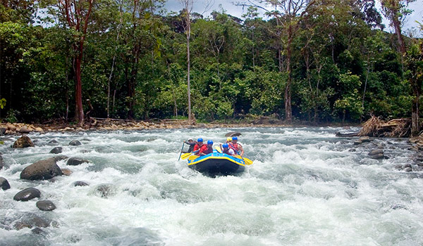 Raft full of people steering down white-water rapids