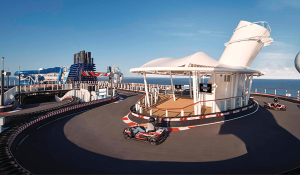 People racing in mini go karts on the top deck of a cruise ship