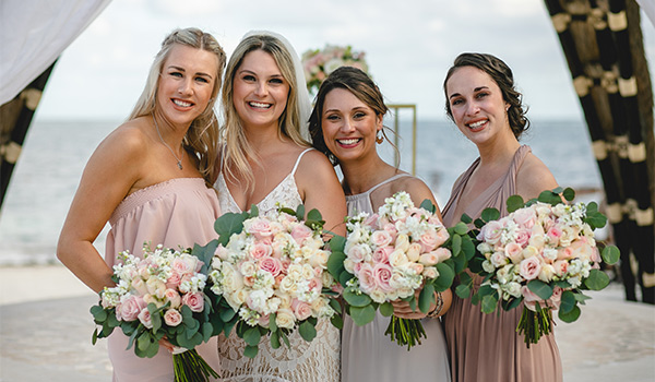 Bride with bridesmaids holding flowers