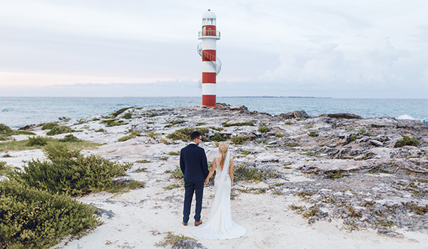 Bride and groom posing in front of a lighthouse by the ocean