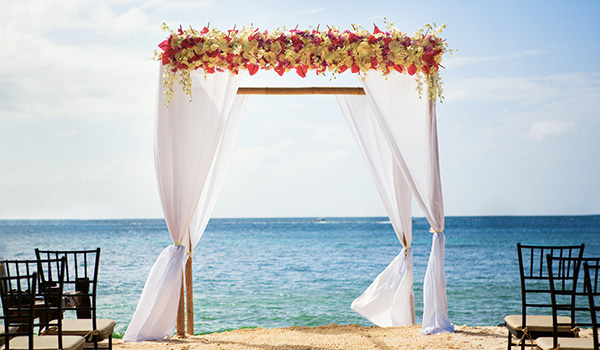 Wedding arch decorated in flowers on the beach