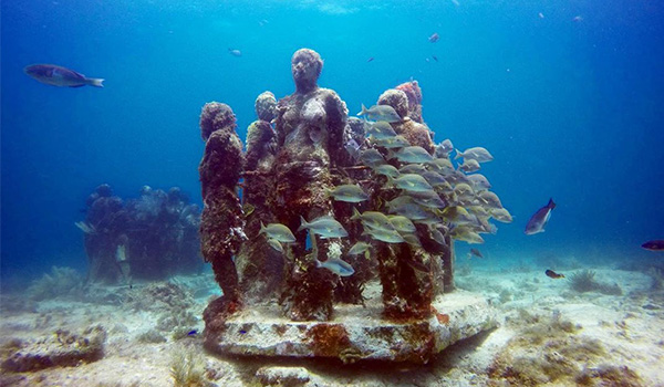 Underwater statues with fish swimming around