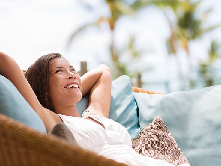 Jeune femme profitant du soleil dans un fauteuil en osier sous un palmier