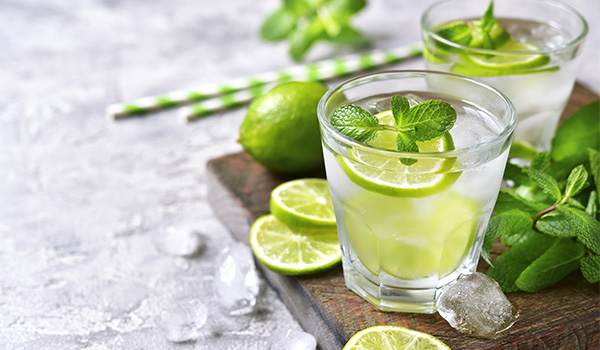 Mojito surrounded by fresh limes and sprigs of mint