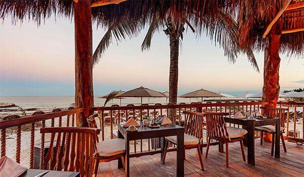 Restaurant sur la terrasse avec vue sur la plage au coucher du soleil