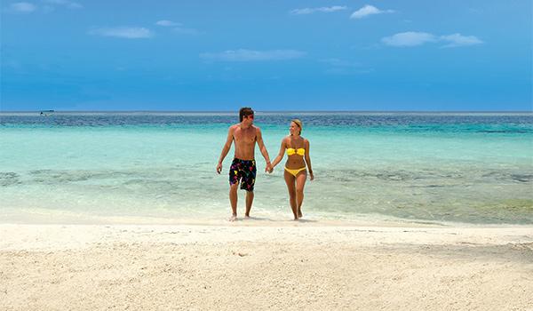 Homme et femme marchant dans l'eau peu profonde à Playa Blanca
