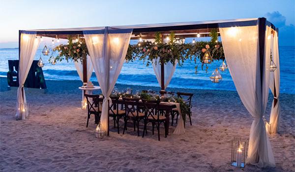 Dinner table under a romantic gazebo on the beach