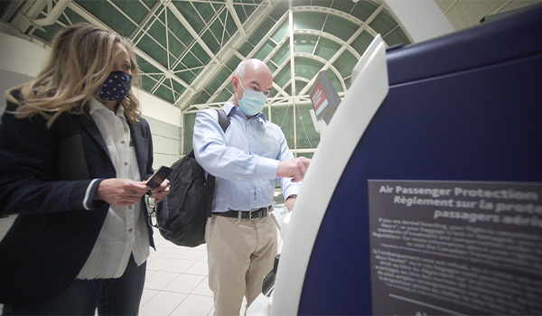 Dr. Nord and his wife using a kiosk to check in at the airport