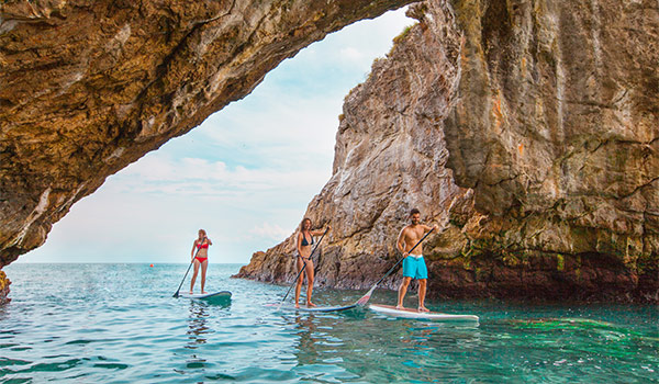 Three people paddle boarding through a cove