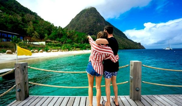 Couple standing on a dock looking out at the Piton Mountains